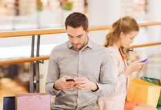 Couple with smartphones and shopping bags in mall. Sale, consumerism, technology and people concept - young couple with shopping bags and smartphones in mall stock image