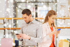 Couple with smartphones and shopping bags in mall. Sale, consumerism, technology and people concept - young couple with shopping bags and smartphones texting Royalty Free Stock Image