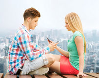 Couple with smartphones sitting on bench over city Stock Image