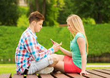Couple with smartphones sitting on bench in park Royalty Free Stock Photography