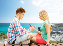 Couple with smartphones sitting on bench Royalty Free Stock Image