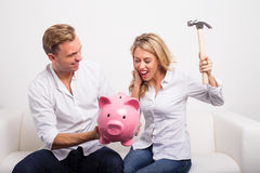 Couple smashing piggy bank with hammer Stock Images