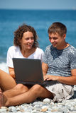 Couple with smile in looking at laptop Stock Photos
