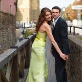 Couple smiles while their pose on the wooden bridge Royalty Free Stock Photos