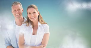 Couple smiling against blue green background with clouds Stock Images