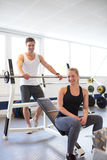 Couple Smiling at Camera After Barbell Exercise Royalty Free Stock Photography