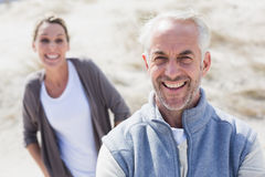 Couple smiling at camera on the beach Stock Image