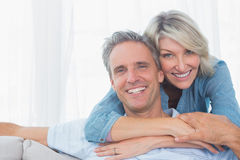 Couple smiling at the camera. At home in living room Royalty Free Stock Photos