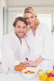 Couple smiling at camera in their bathrobes Stock Images