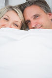Couple smiling at camera from under the covers Stock Photo