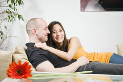 Couple smiling on the couch Stock Photo