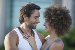 Couple smiling at each other. Oudoor with blurred background Royalty Free Stock Image