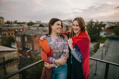 Couple smiling girls staying on city background. Spending good time together on roof, rest and entertainment, family and best friends forever concept. Free Royalty Free Stock Photography