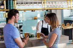 Couple smiling while having beer at counter stock photo