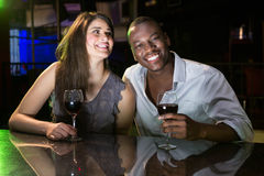 Couple smiling while having red wine at bar counter. In bar Stock Photography