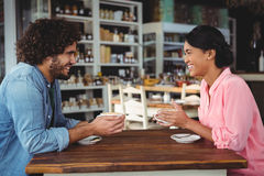 Couple smiling and holding coffee cup. In cafeteria Royalty Free Stock Photos