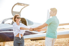 Couple smiling and holding hands on runway near small plane Royalty Free Stock Photos