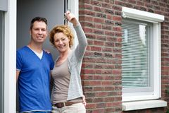 Couple smiling and holding keys to their new house Royalty Free Stock Photography