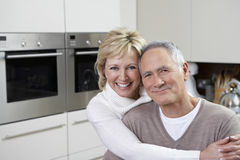 Couple Smiling In Kitchen Stock Photo