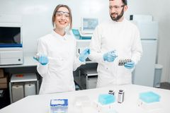 Laboratory assistants working with test tubes. Couple of smiling laboratory assistants in uniform working with analysis in test tubes at the medical laboratory Stock Photos