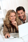 Couple smiling on laptop. Stock Photos