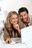 Couple smiling on laptop. Stock Photos
