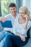 Couple smiling and laughing as they read a tablet Royalty Free Stock Image