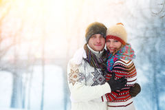 Couple smiling and looking at camera in winter in a forest Royalty Free Stock Photos