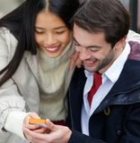 Couple smiling and looking at message on mobile phone together Stock Image