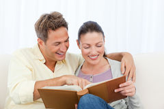 Couple smiling while looking a photo album Royalty Free Stock Photo