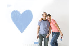 Couple smiling next to heart painted on wall Stock Photography