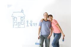 Couple smiling next to house and family painted on wall Royalty Free Stock Images