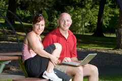 Couple Smiling at the Park - Horizontal. Couple lovingly sitting on a picnic table smiling and sitting at the park. The man is holding a laptop computer Royalty Free Stock Images