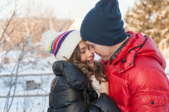 Couple smiling with perfect teeth hugging and looking at camera in winter in a forest Royalty Free Stock Image
