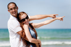 Couple smiling and pointing at the sea Stock Photos