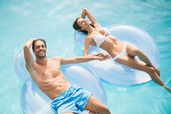 Couple smiling while relaxing on inflatable ring. Young couple smiling while relaxing on inflatable ring at swimming pool Royalty Free Stock Photo