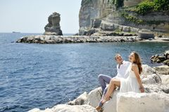 Couple smiling and relaxing near the sea, Naples, Italy Royalty Free Stock Photos