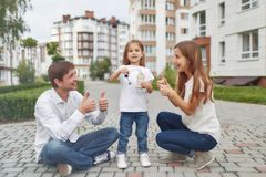 Happy family in front of new apartment building. Couple smiling showing thumbs up their little daughter holding keys to their new apartment. Cheerful family Royalty Free Stock Image