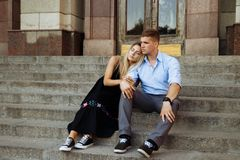 The couple is smiling and sitting on the steps, hugging, dating. love. The couple is smiling and sitting on the steps,hugging, dating. love stock images