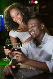 Couple smiling and toasting their wine glasses at bar counter. In bar Royalty Free Stock Image