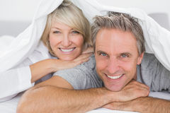 Couple smiling under the covers Stock Photo