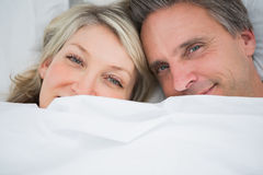 Couple smiling from under the covers Royalty Free Stock Photos