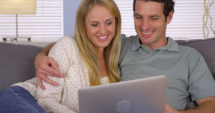 Couple smiling and using laptop on sofa Royalty Free Stock Photography