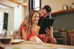 Couple smiling using a tablet pc together in morning Royalty Free Stock Photography