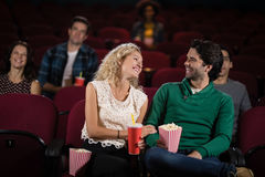 Couple smiling while watching movie in theatre Stock Image