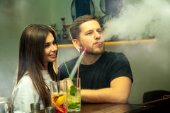 Couple smokes shisha at the bar. Man smokes shisha at the bar while his girlfriend looks at him and smiles Stock Image