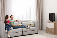 Couple with snack watching TV on sofa together at home. stock image