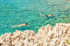 A couple snorkeling in the crystal clear rocky Adriatic sea Stock Photos