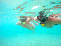 Couple snorkeling. Portrait of a yound couple swimming underwater in the clean blue sea of Protaras, Cyprus. View of snorkeling tube, mask, bikini of free divers Royalty Free Stock Photography