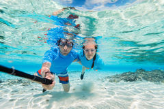 Couple snorkeling. Underwater photo of a couple snorkeling in ocean and making selfie with stick Stock Images